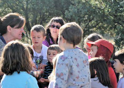 niñas y niños del grupo de juego Aúlla, de Moralzarzal escuchando una explicación de una educadora