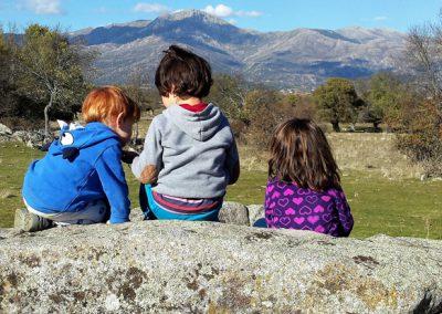 tres niñas del grupo de juego Aúlla, observan la montaña desde la Dehesa de Moralzarzal